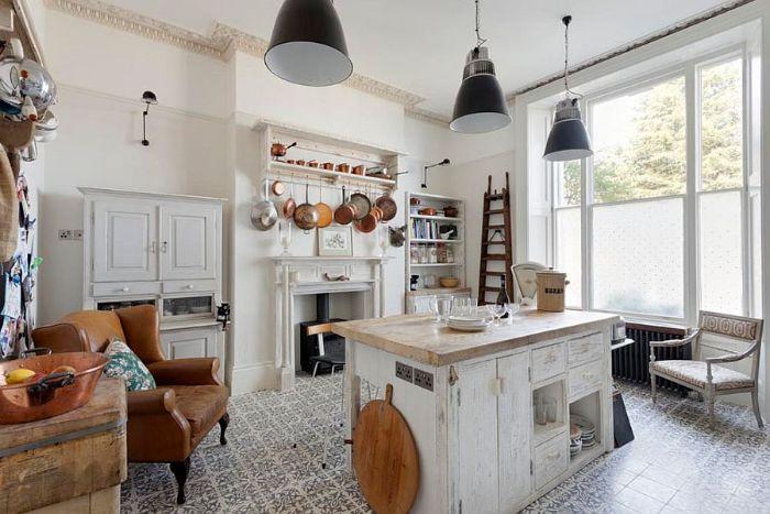 deco campagne cuisine avec ilot central bois brut cheminée blanche sol carrelage original fauteuil cuir marron suspensions ferme