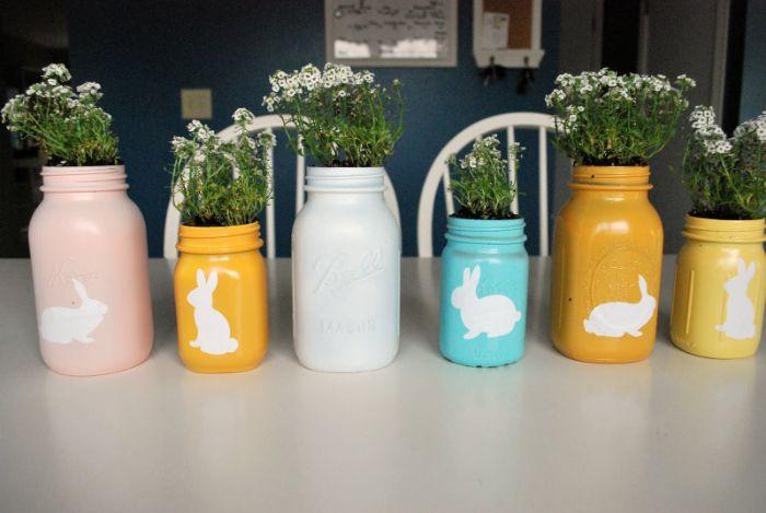 deco table paques originale avec des pots en verre recyclés peints et décorés de motid lapin avec des fleurs à l intérieur