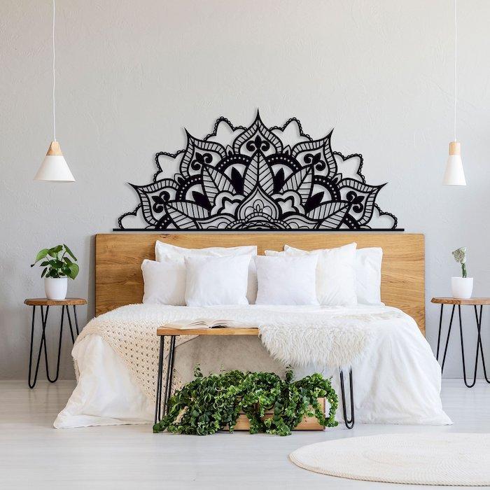 decoration murale mandala noir au dessus d un lit entre deux plantes, déco murale en métal