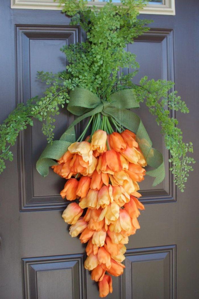 des fleurs oranges nouée d un ruban et suspendus a une porte d entrée en bois