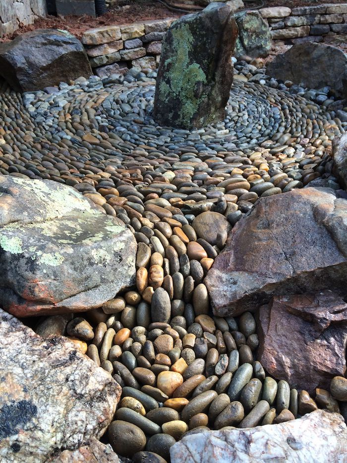 des galets rangées en cercles avec des grandes pierres au dessus idée de déco jaridn