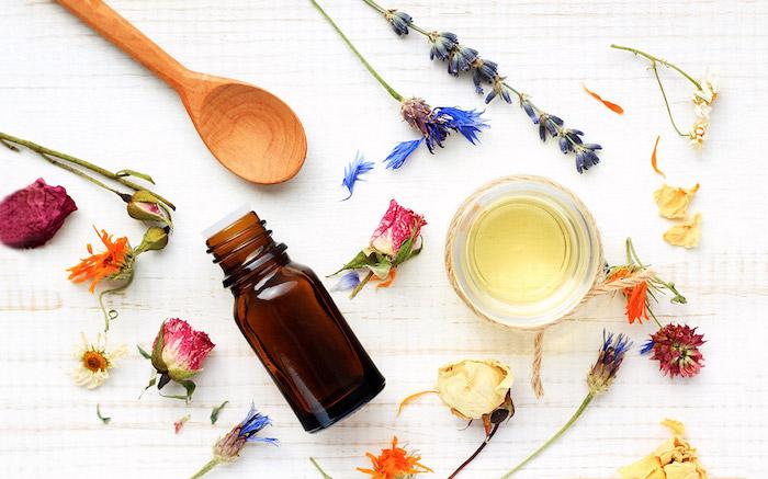 des herbes et des fleurs sur une nappe blnache a coté d une cuillère en bois et un pot d huile essentiel