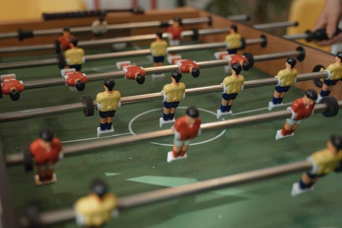des joueurs décoratif de football sur un terrain vert en equipes jqunes et rouges