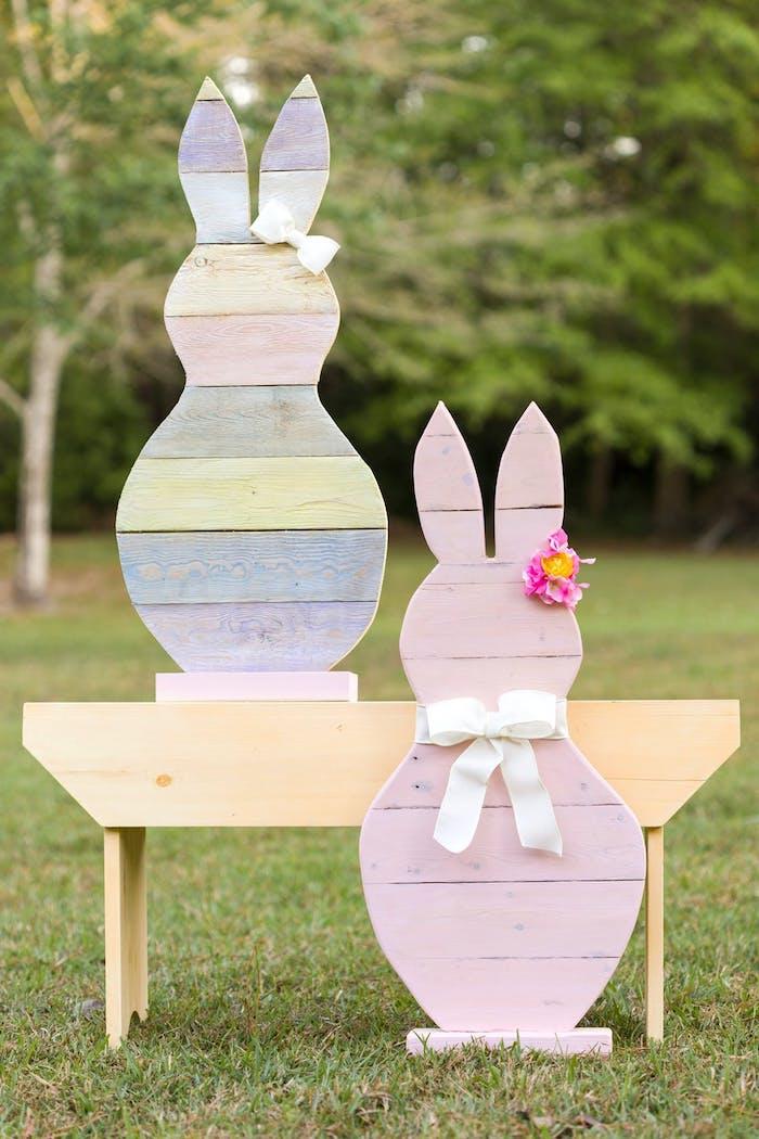 des lapins en bois multicolores dans un jardin création paques décorée avec un ruban et papillon