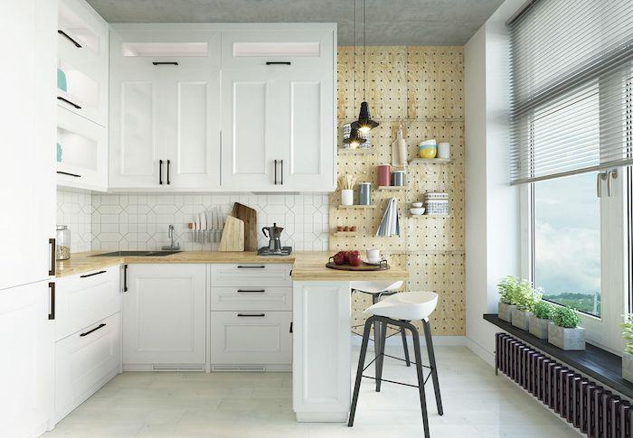 des meubles blanches et grandes fenetres avec des volets roulant dans une petite cuisine équipée