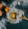 des oeufs cassés dans un tas de farine sur le comptoir a coté d un fouet et cuillère en bois