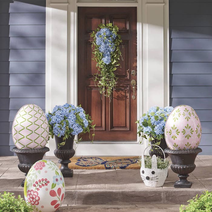 des oeufs gigantesques décoratifs devant une maison peint en violet et des fleurs accorches sur une porte en bois
