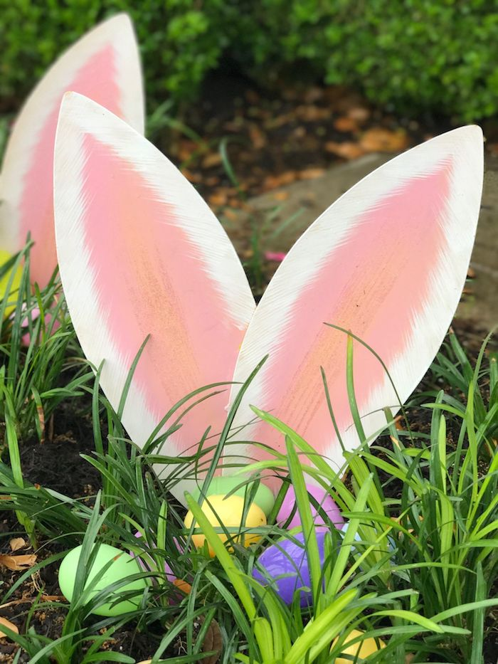 des oreilles de lapin dans le jardin entoures de l herbe et des oeufs teintés deco paques diy