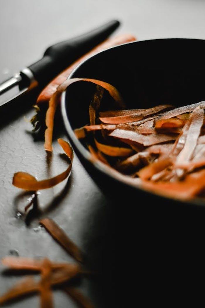 des pelures des carotes dans un bol a coté d un eplucheur de legumes