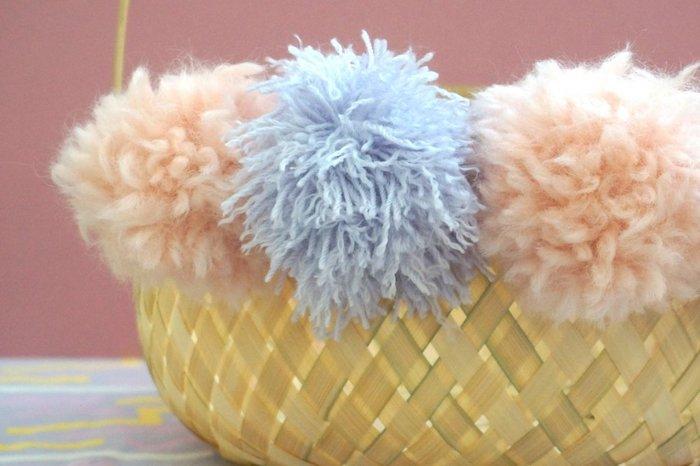 des pompons en fil rose et lavande accroché a un panier tissé bricolage paques primaire