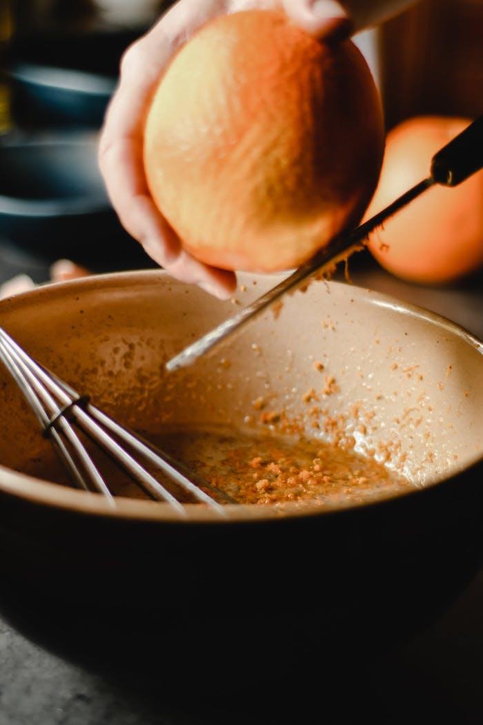deux mains qui rapent l ecorce d un orange au dessu d un bol