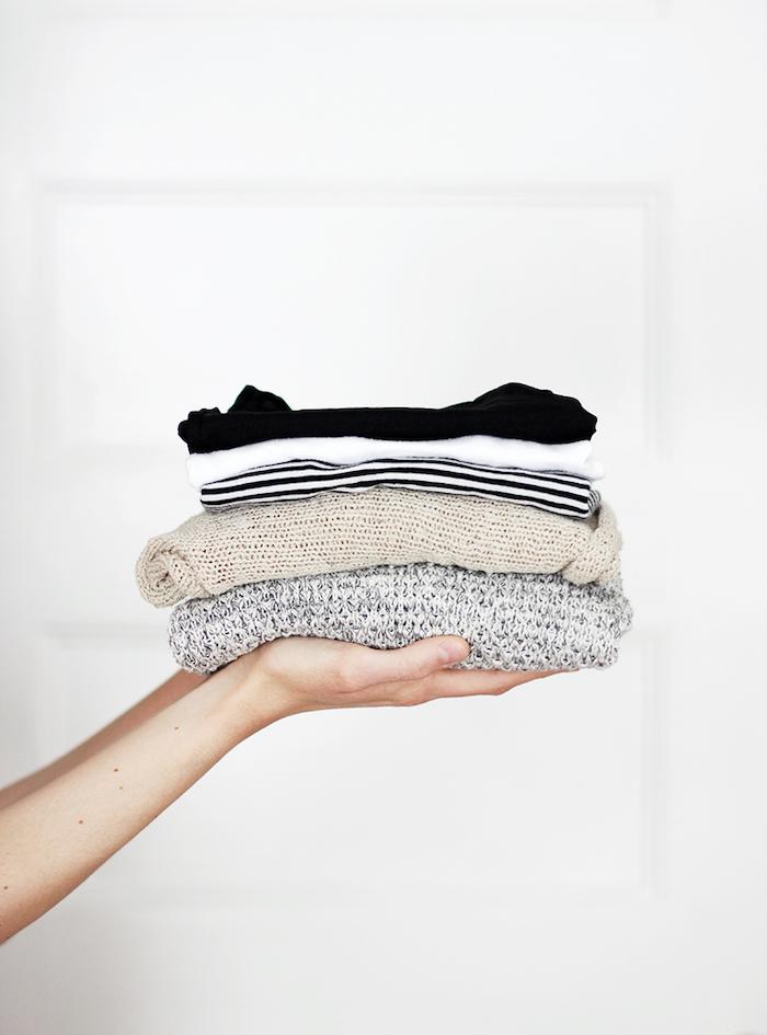 deux mains qui tiennent des blouses tricotés pliés elements d un style minimaliste femme