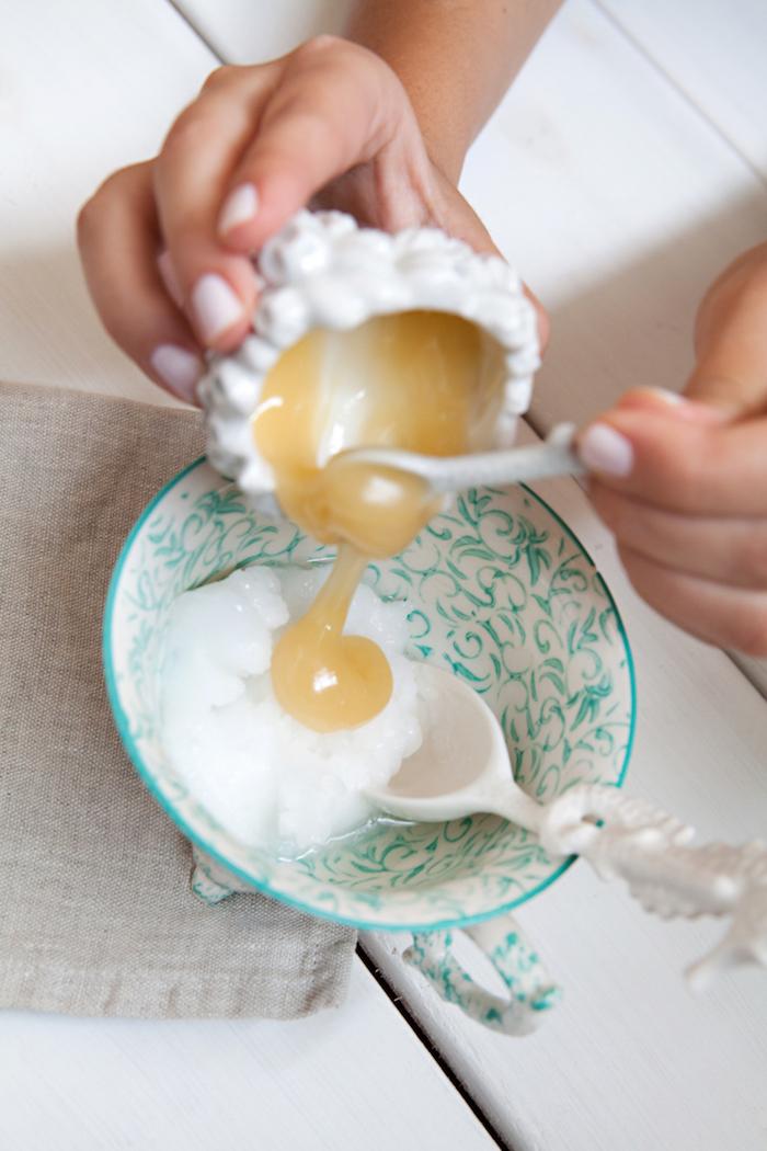 deux mains qui versent de miel dans une coupe des ornements bleus pour un masque capillaire maison