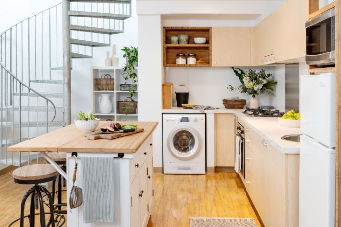 escalier colimaçon appartement à petite cuisine équipée couleur crème ilot central blanc avec tabourets industriels