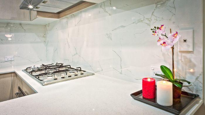 exemple de credence cuisine en marbre balnc dans une cuisine au plan de travail blanc et façade bois clair