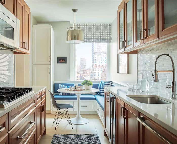 exemple de cuisine aménagement en l avec un banc et des coussins bleus et des meubles en bois