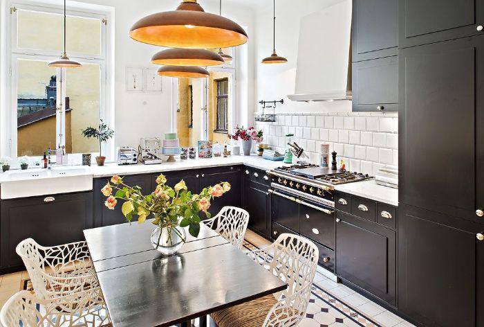 exemple pour aménager sa cuisine noire au carrelage blanc suspensions laiton table bois chaises metalliques blanches