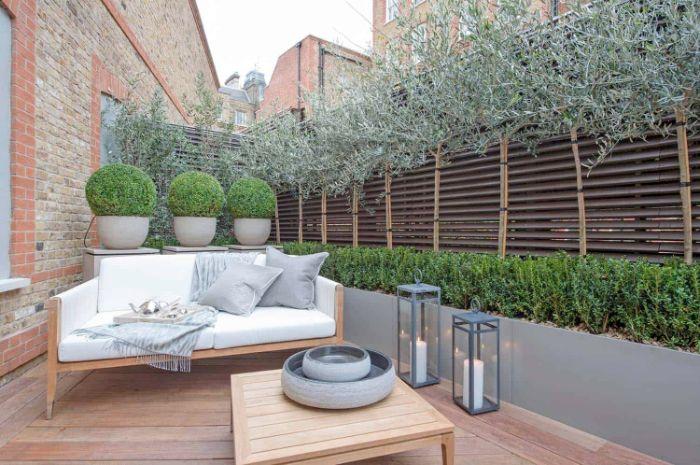 exemple terrasse revêtue de bois avec canapé banc bois table basse bois lanternes avec bougies brise vue plantes bois
