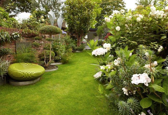fauteuil vert confortable gazon vert et parterre de fleurs et arbustes sauvages arbres couverts de verdure