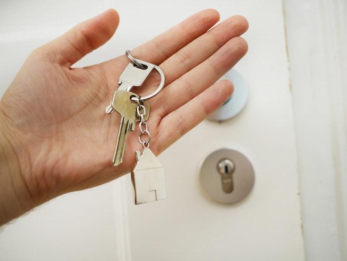 femme qui tiens les cles pour son appartement porte d entree blanche