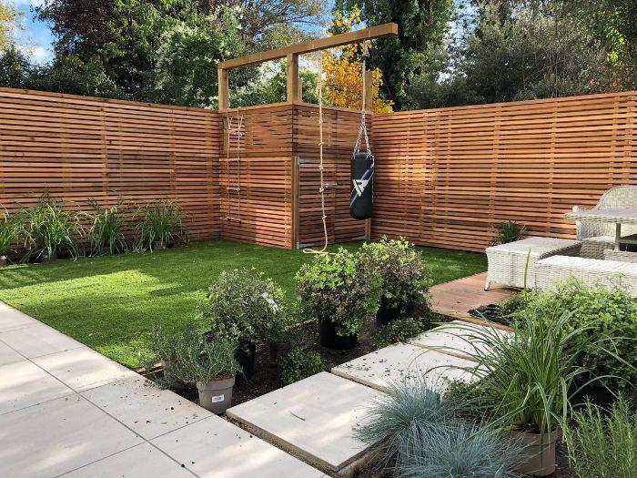 gazon vert entouré de buis chemin de dalles de béton salon de jardin résine tressée palissade bois