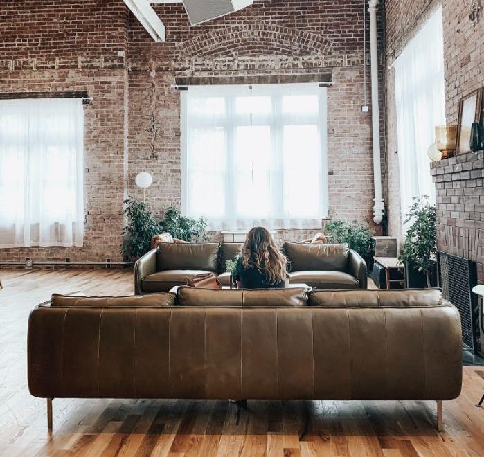 grand espace deco salon industriel cocooning avec des canapés de cuir marron parquet clair murs de briques plafond blanc.jfif
