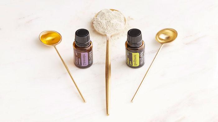 huile cheveux secs avec trois cuillères d orées plaines avec farine et miel sur un comptoir en marbre