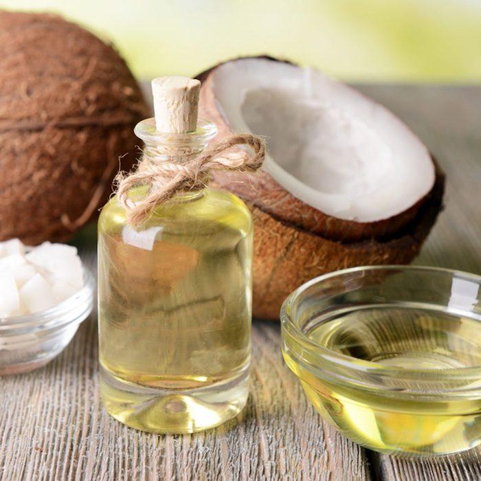 huile cheveux secs huile de coco dans une bouteille a coté d un noix de coco cassé