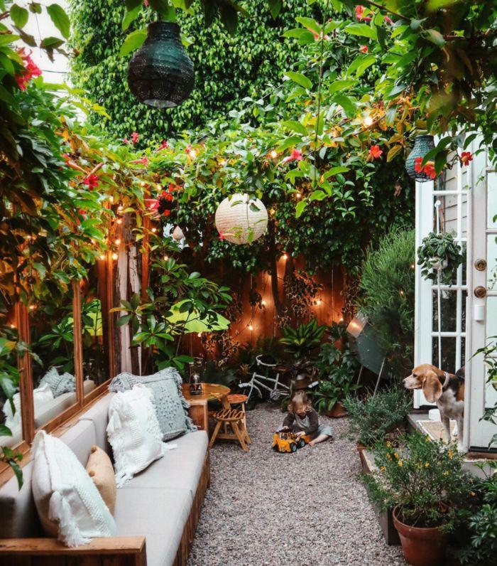 idée comment aménager un petit jardin de 10 m2 avec banc en bois végétation verte palissade guirlande lumineuse parterre de gravier