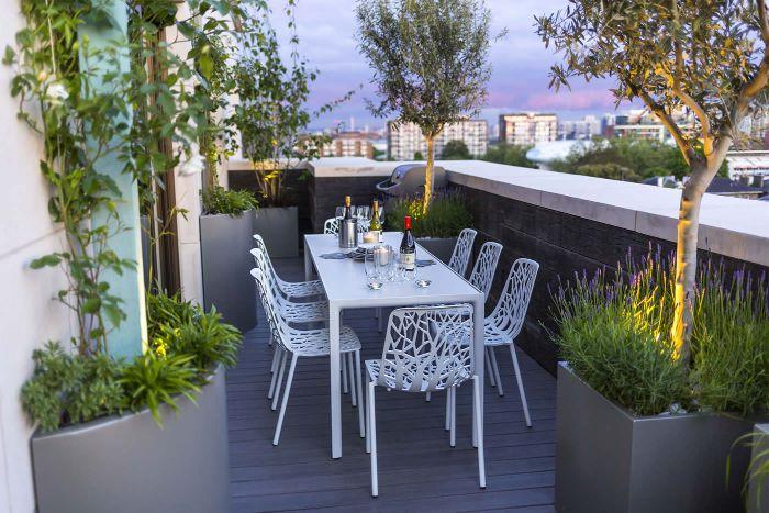 idée pour aménager sa terrasse plancher bois chaises et table blanche arbres en pot de terrasse