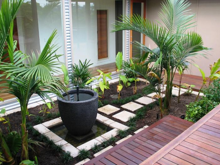 idée pour aménager un petit jardin de 20 m2 avec terrasse en bois chemin de dalles au milieu de plantes vertes