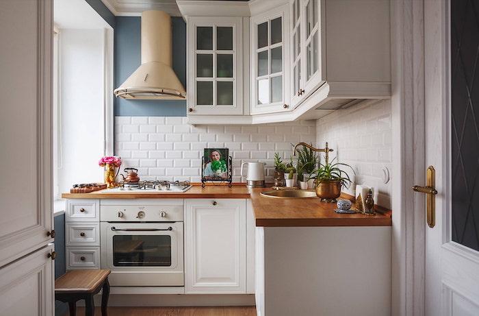 idée rangement petite cuisine d angle avec des comptoirs en bois et des meubles blanches un aspirateur beige au mur