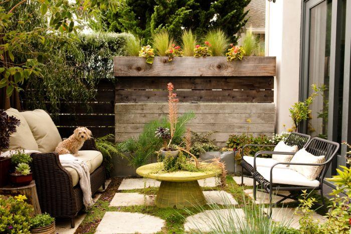 idee amenagement jardin avec chaises metaliques canapé en résine tressée mur palissade bois dalles de pierre sur gazon multitude de plantes
