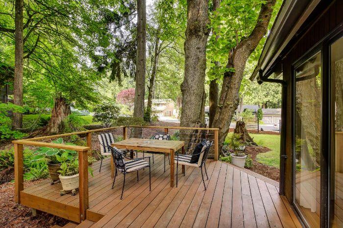 idee deco terrasse simple avec chaises en metal et table bois sur une terrasse de bois devant maison entourée de vegetation