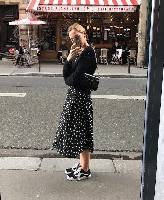 jeune femme qui se prend photo dans une vitrine et porte des baskets avec une jupe a pois