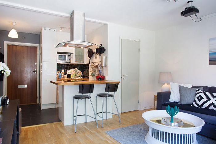 kitchenette pour studio 20 m2 avec carrelage noir meuble cuisine blanc ilot chaises noires ouverture sur salon gris et blanc