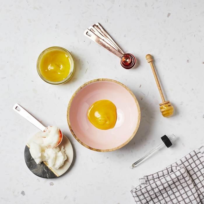 le processus de mixture d un masque miel cheveux avec d huile de coco une serviette a carreaux a coté