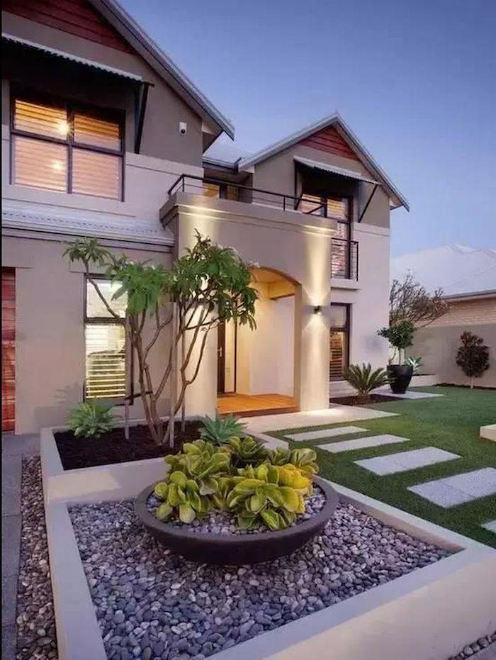 maison ultra moderne avec de pelouse devant et un carré décoratif rempli des cailloux
