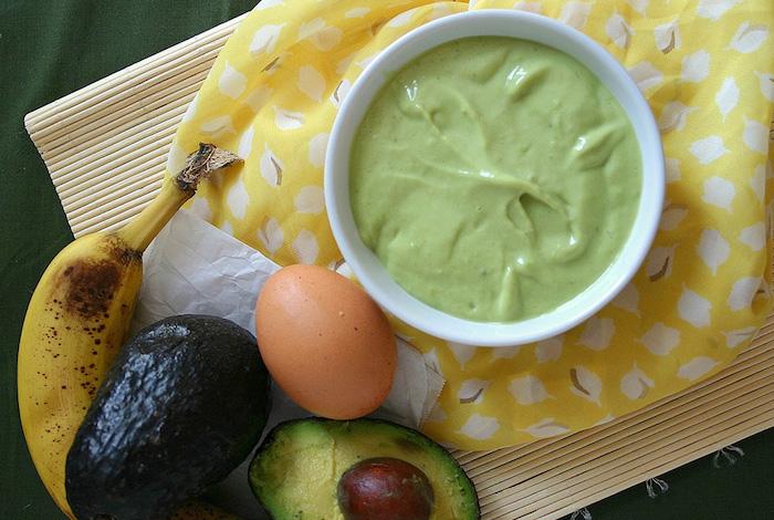 masque banane cheveux avec de l avocat et des oeufs une mixture verte sur serviette aux motifs