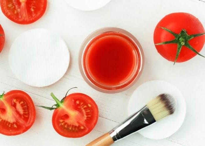masque cheveux secs au jus de tomates des tomates coupés et une brosse sur un tampon de coton