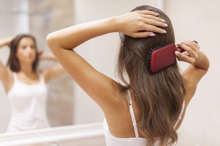 masque cheveux secs une femme devant le miroir peigne ses cheveux avec une brosse, masque maison pour cheveux secs