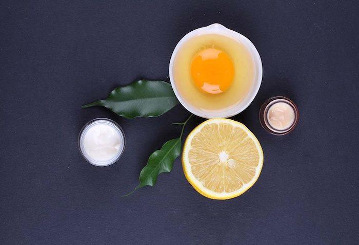 masque maison cehveux secs a la base de citron et de jaune d oeuf sur une surface bleu fonce
