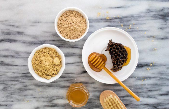 masque miel cheveux quelques coupes en porcelaine et un pot de miel sur un comptoir en marbre