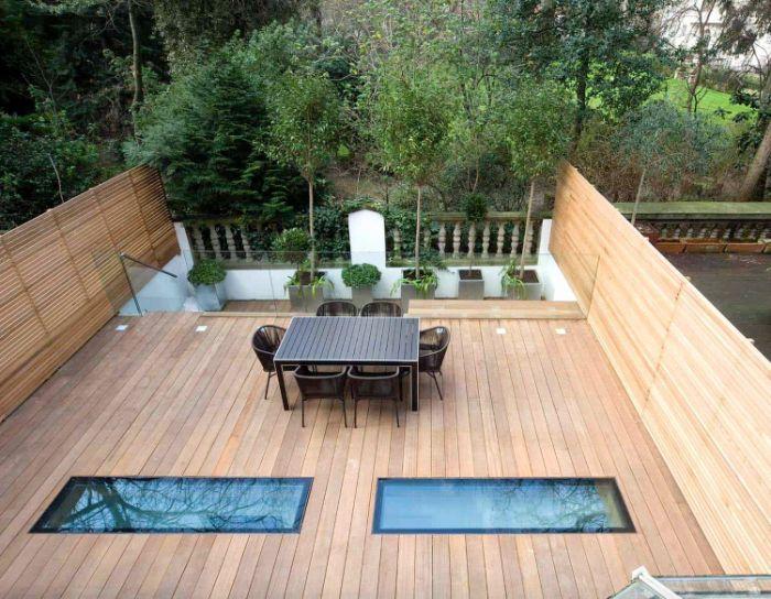 modèle terrasse bois en hauteur avec chaises tressées table salle à manger sol bois plantes en bacs de béton