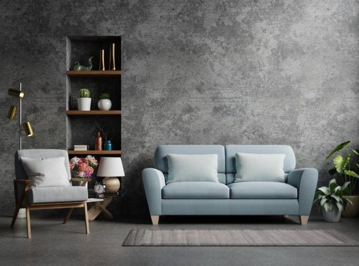 mur de béton canapé bleu fauteuil gris étagère bois et métal sol gris exemple de déco industriel chic