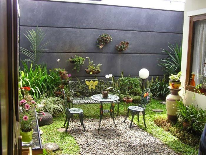 mur de cloture de beton gravier table et chaises metalliques gazon vert arbustes et plantes