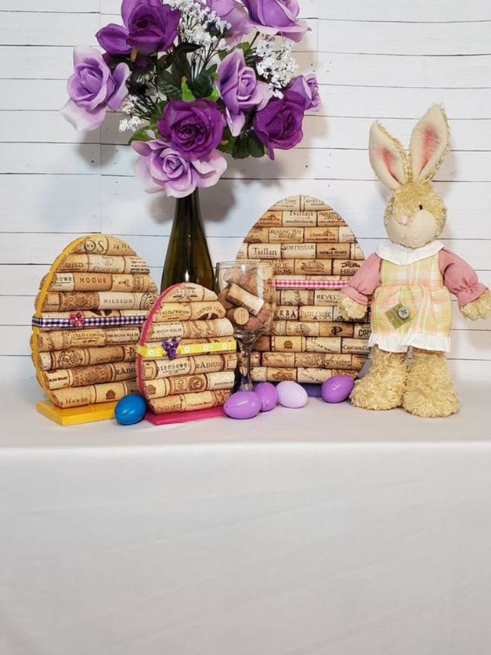 oeufs de paques en bouchons de liège recyclés sur planche de bois oeufs plastique fleurs violettes et figurine lapin paques