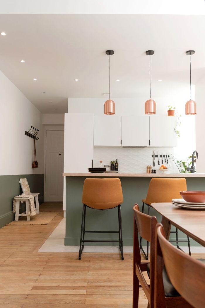 pan de mur et ilot central gris cuisine blanche avec des suspensions cuivre et salle à manger bois