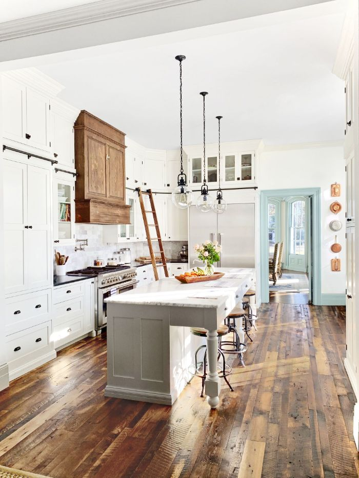 parquet bois brut et hotte de cuisinebois dans une cuisine retro chic champetre de couleur blanc avec suspensions et tabourets bar industriels
