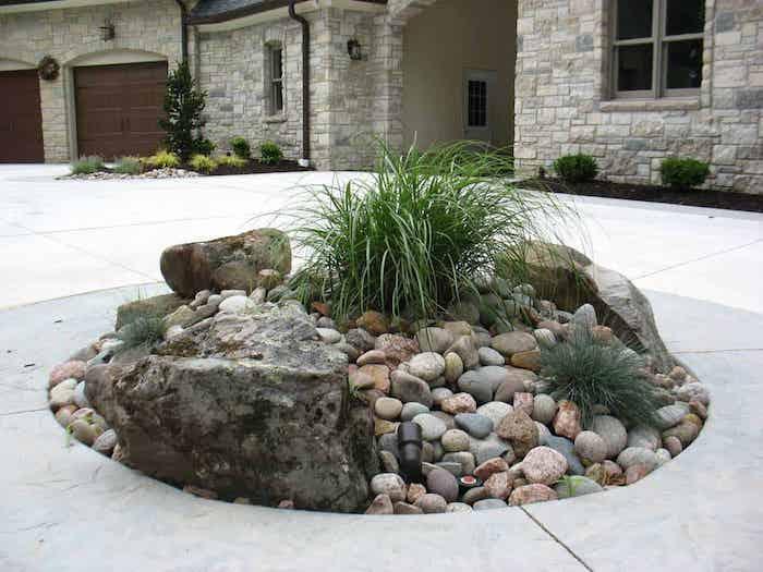parterre de fleurs avec cailloux en forme ronde devant une maison en pierre